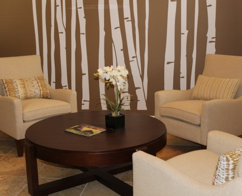 Modern sitting room featuring birch tree decals on accent wall