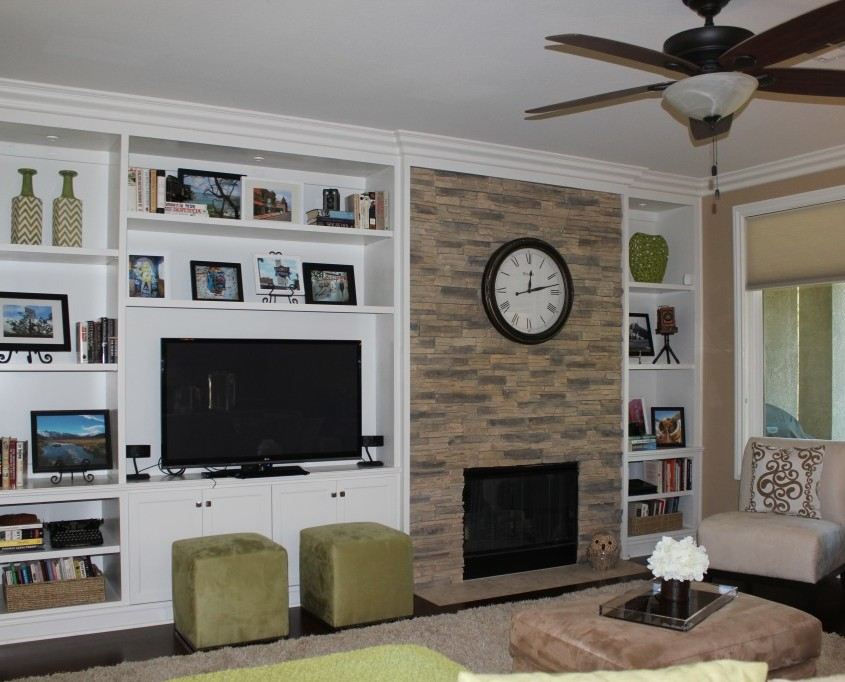 Modern living room features custom cabinets and stone fireplace