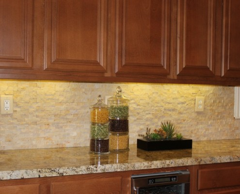 Kitchen remodel featuring granite counters and stacked travertine backsplash