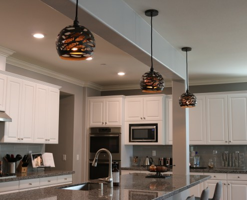 Beautiful modern, black and copper pendant lights from Uttermost hang over long kitchen bar. Stools form Living spaces.